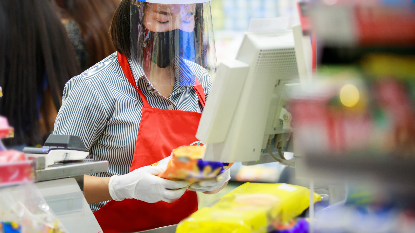 Cashier worker wearing a Silenta face shield visor.